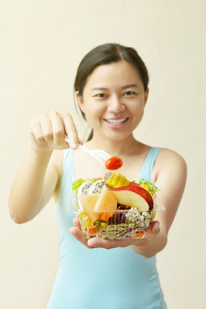 Asian woman with happy face holding fresh salad box