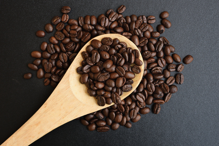 Roasted coffee beans in wood spoons on black table, Top view. Stock Photo
