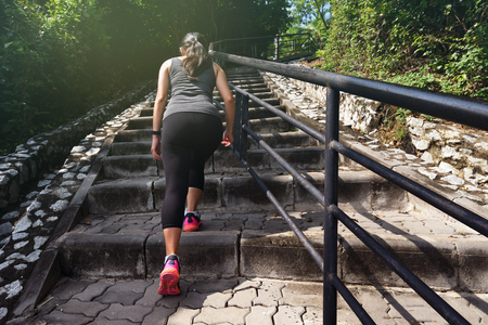 Healthy lifestyle sports woman going up on stone stairs