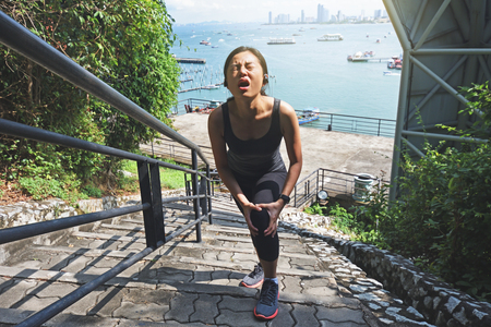 Woman crying for a painful knee injury while exercising and running. Stock Photo