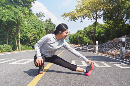 Young fitness woman stretching her leg on road  in morning before  jogging outdoor in nature