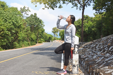 Athlete woman drinking water from a bottle after jogging in the park on a sunny day
