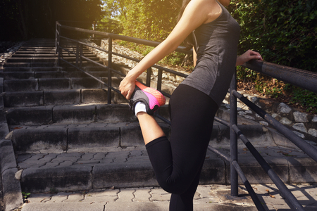 Young woman runner stretching legs before began her run Stock Photo