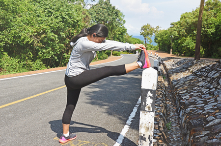 Young woman runner stretching legs before running outdoor in the forest mountain road. Stock Photo