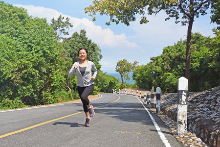 Young fitness woman running on mountain road in beautiful nature.