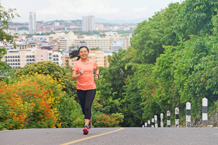 Young  woman running outdoors in park with city scene background