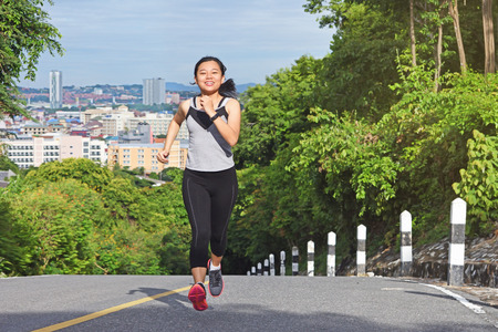Young asian woman jogging in park smiling happy running and enjoying a healthy outdoor lifestyle.