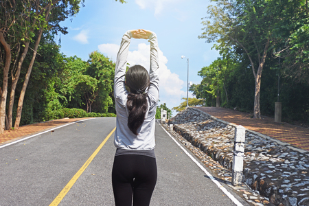 Young fitness woman runner warming up on road stretching arms before run Stock Photo