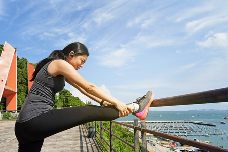 Woman stretching her leg before before running on sunny day. Stock Photo