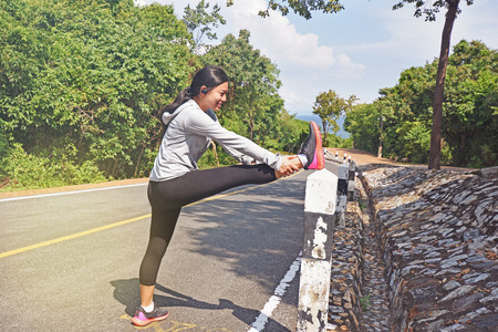 Woman is stretching before jogging in the forest mountain road Stock Photo