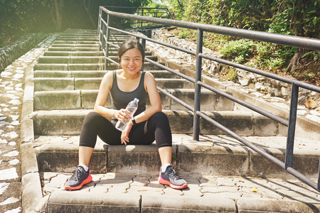 Sporty asian  woman sitting outdoors resting drinking water bottle after morning run Stock Photo
