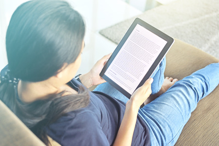 Woman relaxing at home reading an e-book online on her tablet