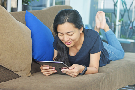Woman is reading the e-book lying on the sofa Stock Photo