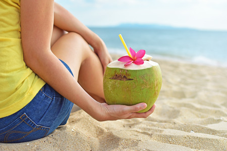 Young woman drinking fresh coconut water and sitting on the beach.