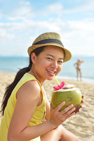 Woman drinking coconut water having fun on summer vacation.