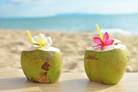 Coconut fruit with flower on wood table with blue sea and sky background Stock Photo