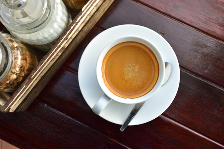 White coffee cups full of fresh espresso in sunshine light, top view on old wooden table Stock Photo