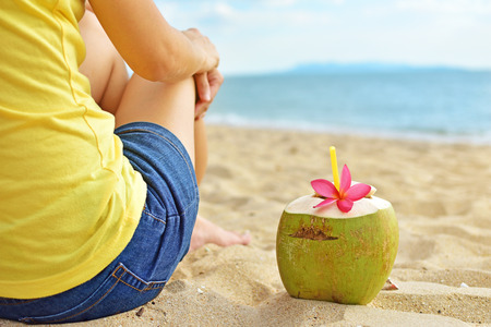 Young woman relaxing on the beach with coconut juice on summer vacation. Stock Photo