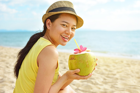 Happy woman drinking fresh coconut water and sitting on the beach Stock Photo
