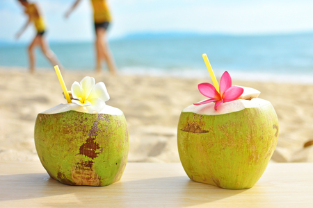 Tropical fresh coconut cocktail decorated plumeria on summer beach