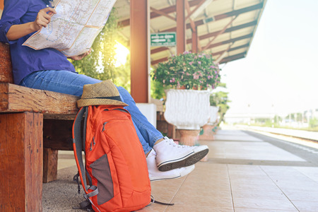 Young traveler sitting with map and backpack at the train station, waiting for a train. Stock Photo