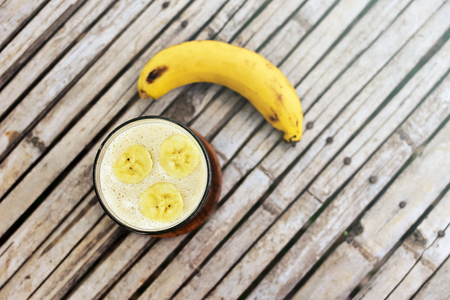 Banana smoothie and fresh banana on wooden background. Top view.