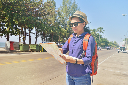 Beautiful woman traveler holding location map in hands while looking for some direction in urban scene in sunny summer day