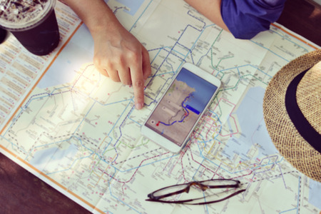 Young woman planning  vacation trip with map and cell phone