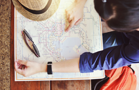Tourist planning vacation with map choose where to travel and bag waiting for train