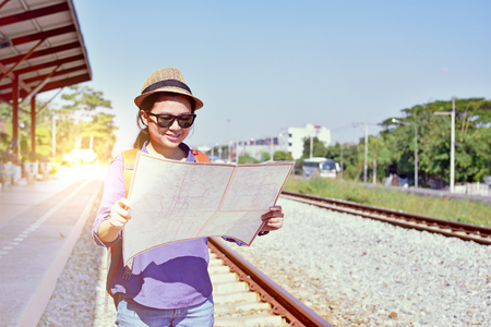 Cheerful woman traveler holding location map in hands while looking for some direction in Thailand scene in sunny summer day