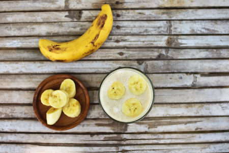 Healthy smoothie with banana on wooden background.