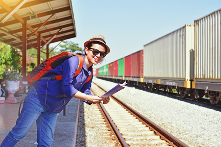 Young woman traveler with backpack and hat holding map with train background Stock Photo