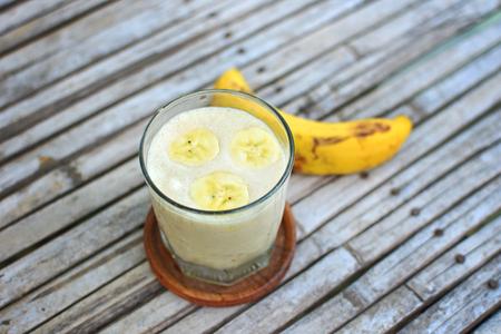 Fresh made Banana Milkshake on vintage wooden background