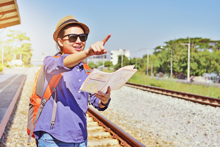 Asian backpack traveler woman holding generic local map and waving hand at train station platform, summer holiday travelling. Stock Photo
