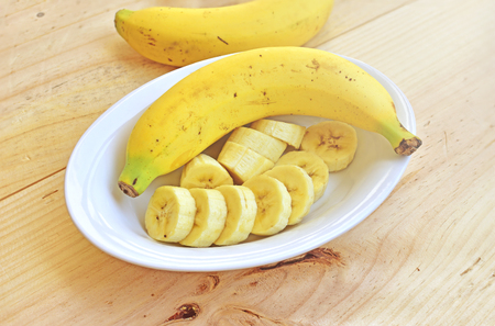 A banch of bananas and a sliced banana in a bowl over a wooden table.