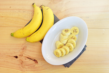 Top view of a bowl of sliced ripe banana on wooden background. Stock Photo