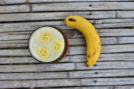 Healthy breakfast Banana smoothie in glass with fresh fruits on wooden background