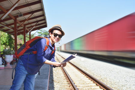 Young woman traveler with backpack standing on train station with map while waiting for train