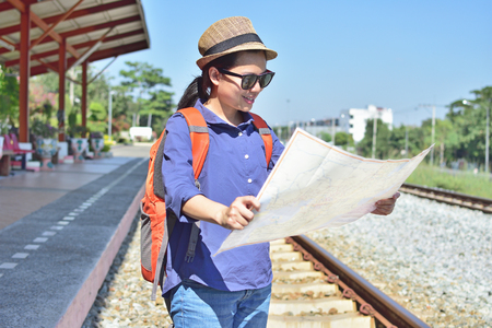 Woman traveler holding location map in hands while looking for some direction with  backpack