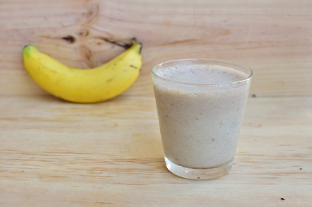 A Glass of fresh banana fruit smoothie on a rustic wooden background. Stock Photo