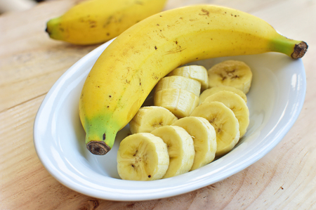 A sliced banana in a bowl on wooden background Stock Photo