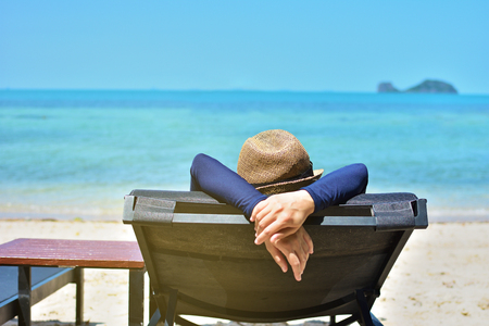Woman relaxing on a tropical beach with hat Stock Photo