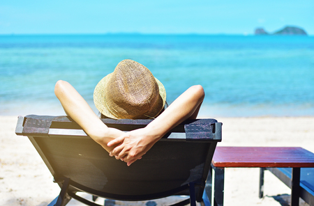 Summer day lifestyle woman relaxing in deck chairs on the beach
