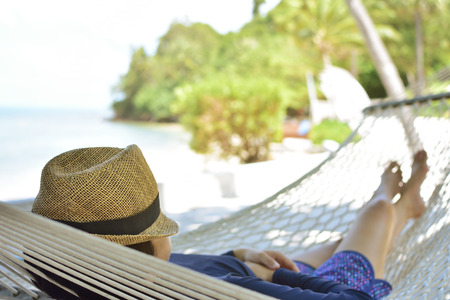 Woman relaxing on hammock with hat on vacation