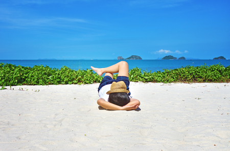 Sleeping woman relaxing on beach ocean background.