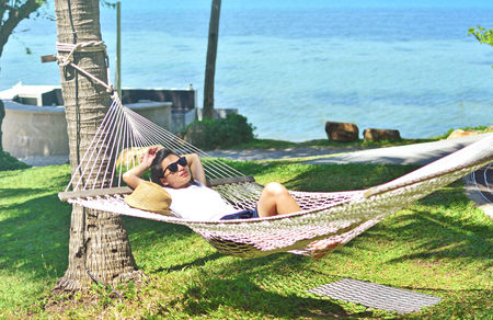Woman relaxing in the hammock on tropical beach at Samui islands, Thailand