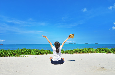 Happy woman sitting arms outstretched back and enjoy life on the beach at Sea