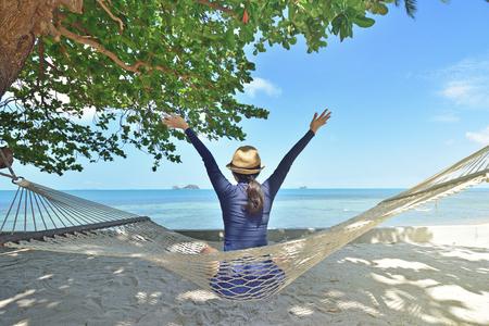 Happy woman in a hammock enjoying vacation on tropical beach