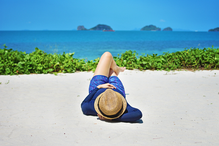 Woman laying on white sand  in beach  hat enjoying summer holidays