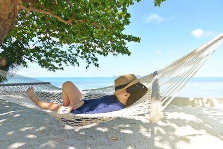 Happy woman in hammock on tropical paradise beach Stock Photo
